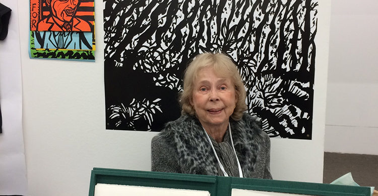 Stevens behind open copy of her livre d'artiste, ERANOS. ERANOS (2000) is a limited edition, boxed short story with original etchings. There are posters of her ink drawings from her 2015 paperback;THE SIXTIES IN BLACK AND WHITE: DRAWINGS BY ELISABETH STEVENS on the wall behind.